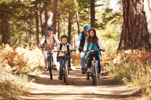 Grandparents and kids cycling on forest trail, California